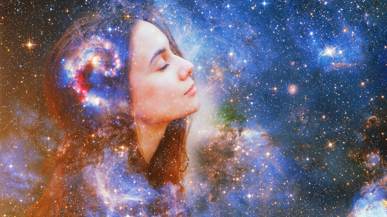 Double exposure image of a woman with her eyes closed overlaid across outer space