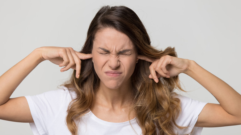 woman plugging her ears with her fingers, looking annoyed by a sound