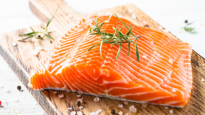 raw salmon fillet on a butcher's block with rosemary