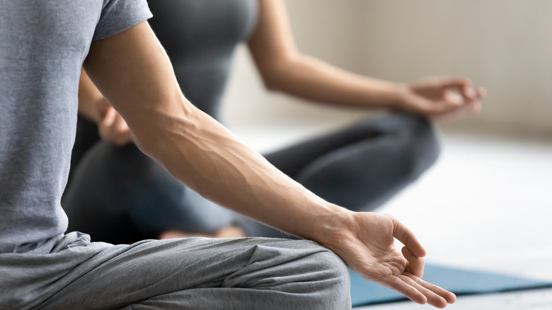 Close up of the hands of two people in a yoga class