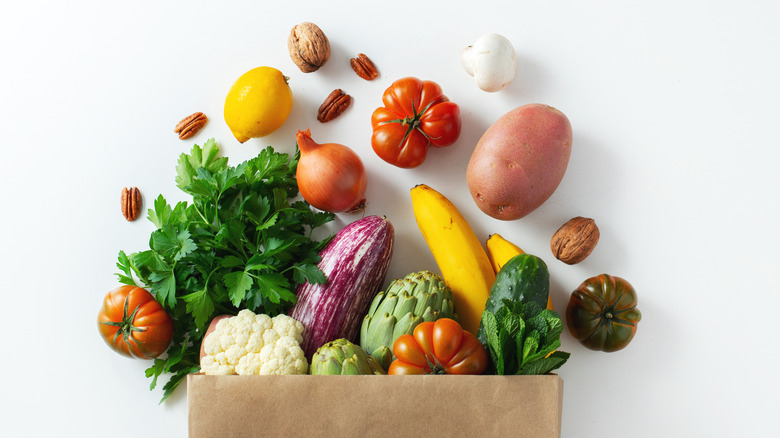 paper bag of groceries spilling out healthy foods