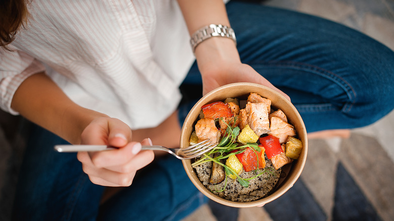 Woman sitting on the floor with bowl of healthy food