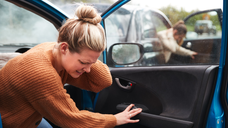 Woman getting out of car, holding her neck