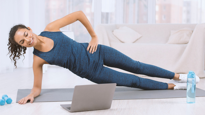 A woman doing a side plank on a yoga mat while looking at a computer