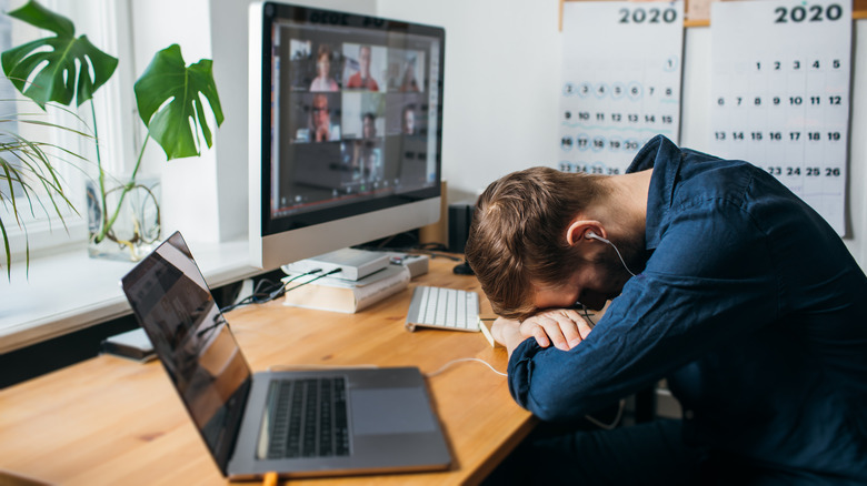 Man sleeping on his desk during a video call