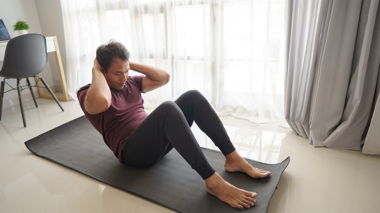 Man on yoga mat at home doing a sit-up