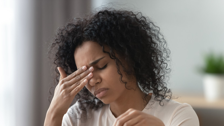 Woman grimacing with closed eyes and hand on face