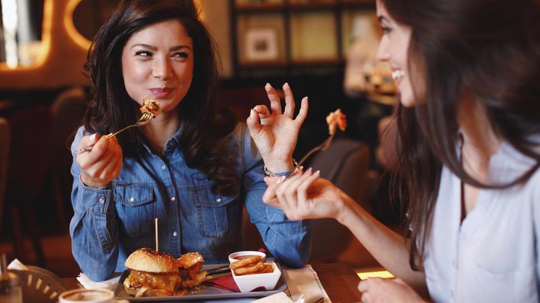 Two women enjoying burgers