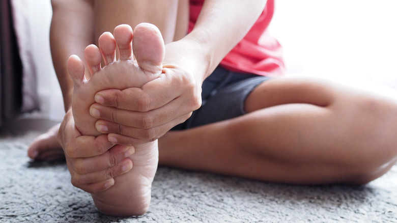 woman massaging foot while stretching