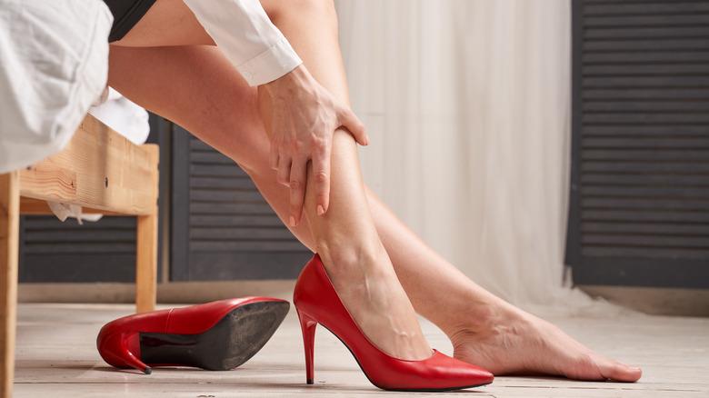 woman holding leg, cramp