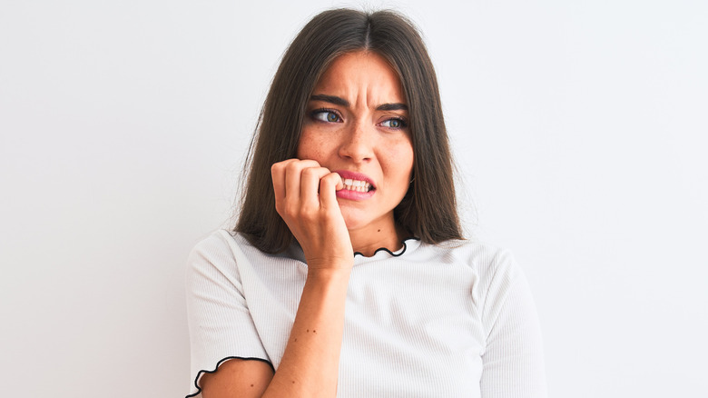 Concerned young woman biting nails
