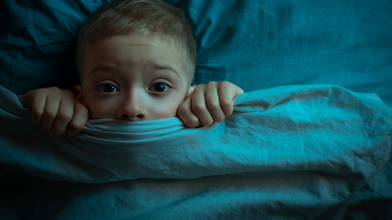 Child in bed under covers