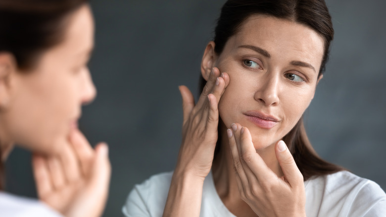 A concerned looking middle-aged woman checking her skin