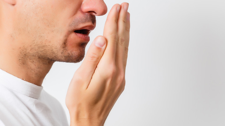 close up of a young man breathing on his hand to check his breath