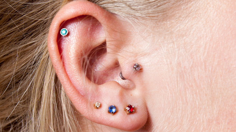 Close-up of woman's ear with multiple colorful earring studs