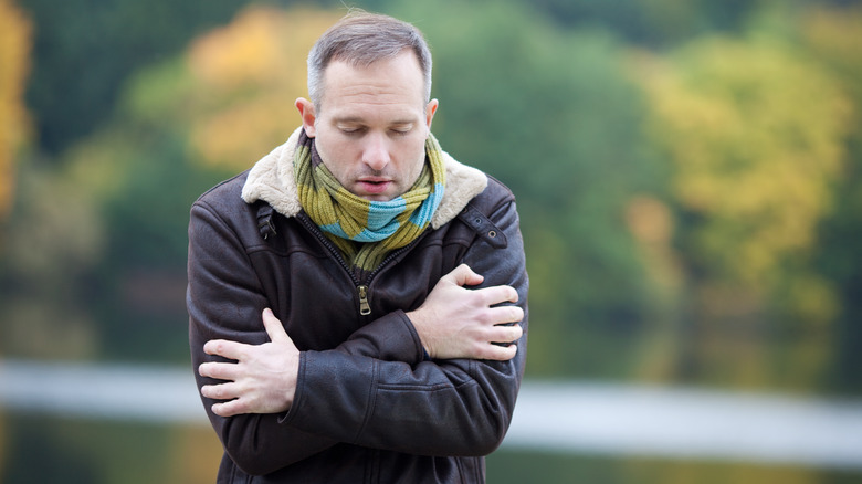 Man in winter clothes hugging himself
