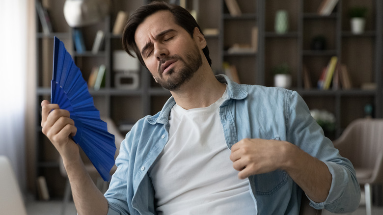 Man feeling uncomfortably warm fanning himself in front of his laptop