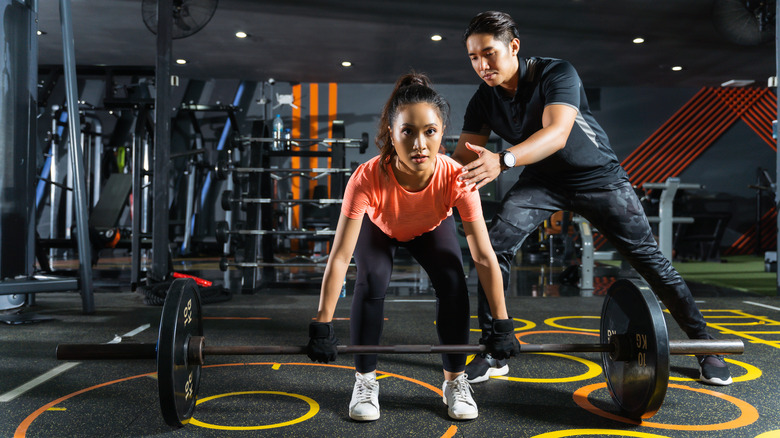 A trainer helping a client with a deadlift
