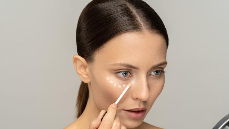 A woman applying face primer