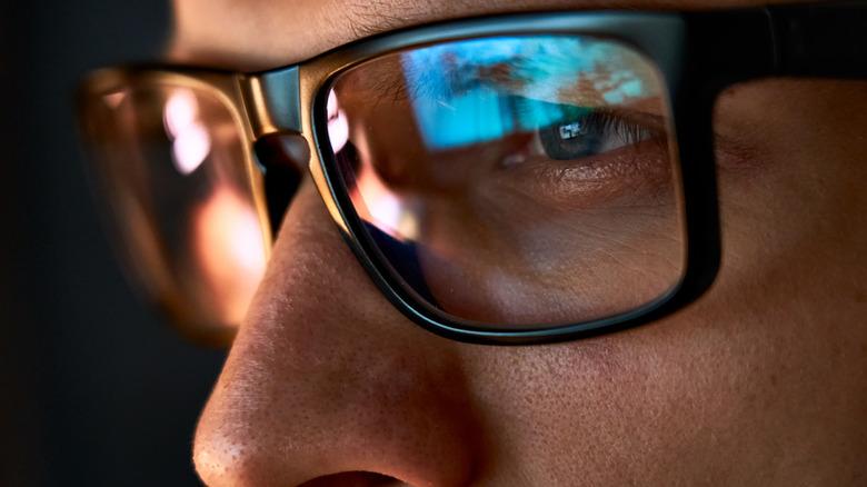 Close-up of man looking at screen at night