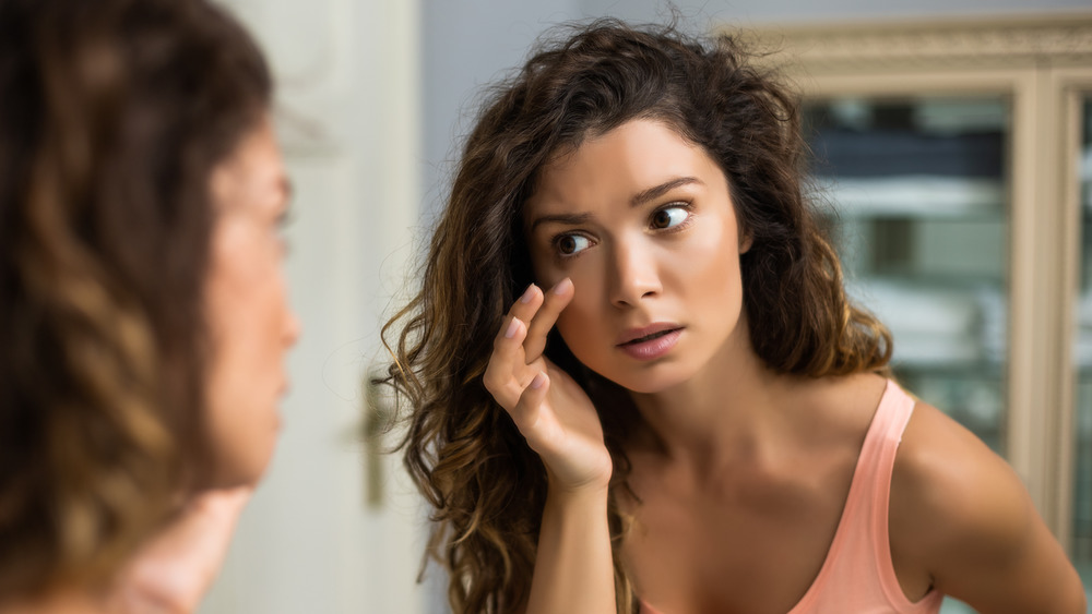 woman looking in mirror at eye