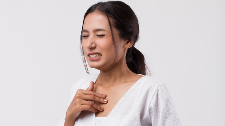 Young woman clutching her chest and stomach in pain