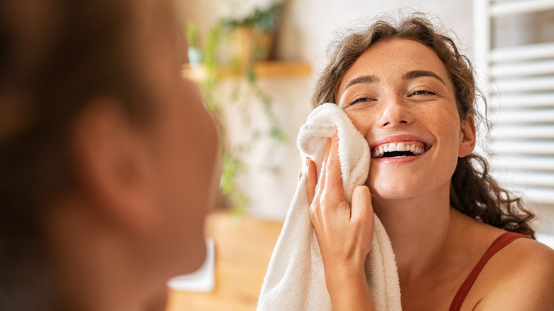 A woman wipes her face with a towel