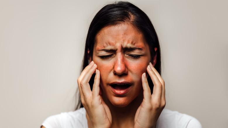 Woman touching sunburn on face
