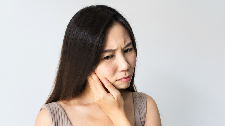 A woman cradles her jaw to indicate oral discomfort