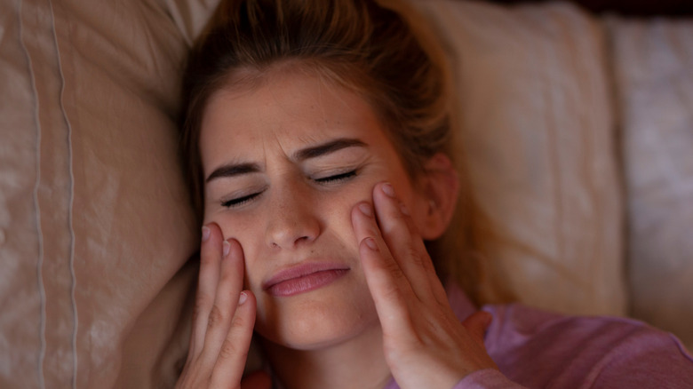 Woman clenching her jaw in bed