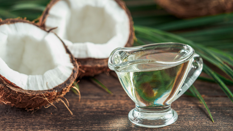 Liquid MCT oil and halved coconut on wooden table