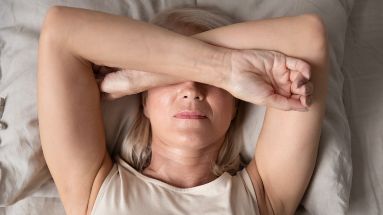Woman laying in bed with hands over face