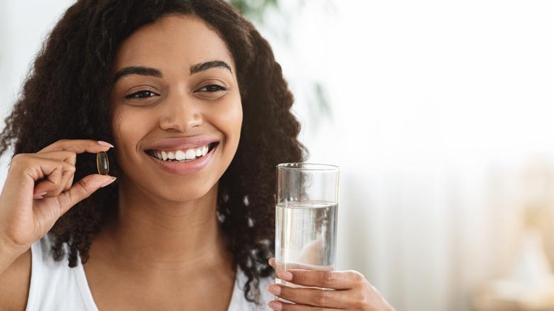 woman shaking vitamins into hand