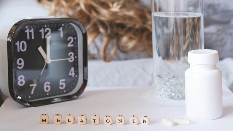 """an alarm clock, glass of water, pill bottle, and the word """"melatonin"""" spelled out on the night table"""