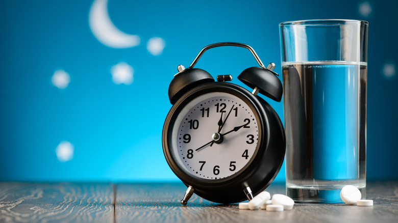 pills, glass of water, and alarm clock with nighttime background