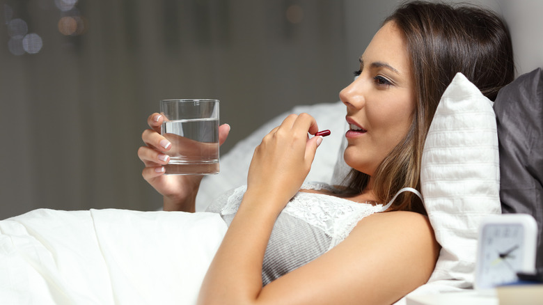 woman taking pill while laying in bed