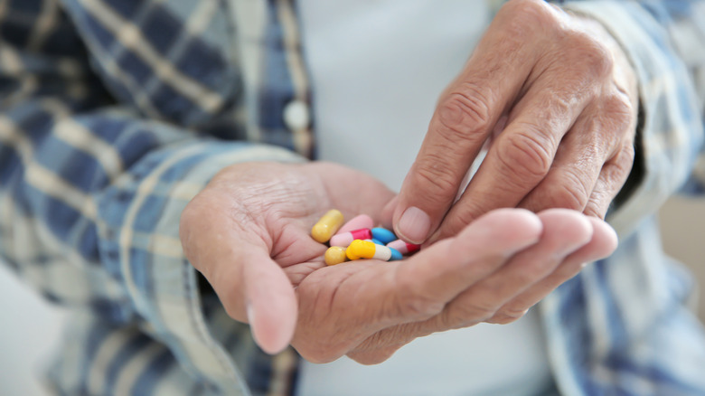 man's hand holding many different medications