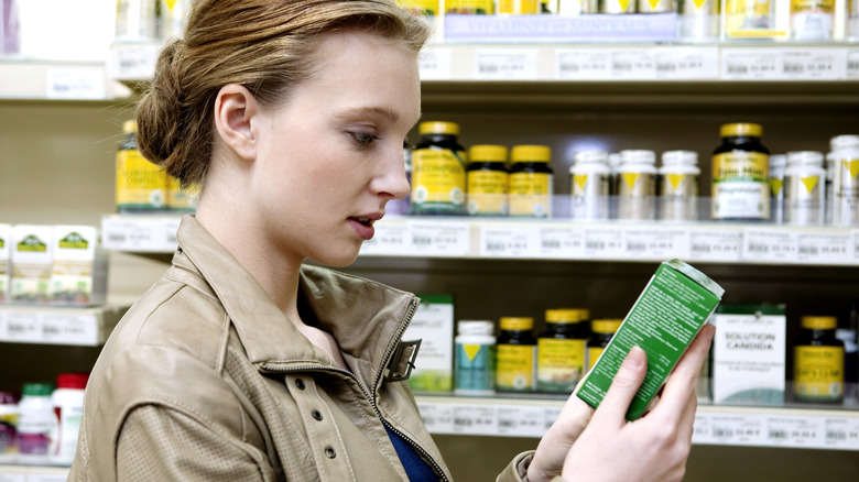 woman reading supplement box label in a store