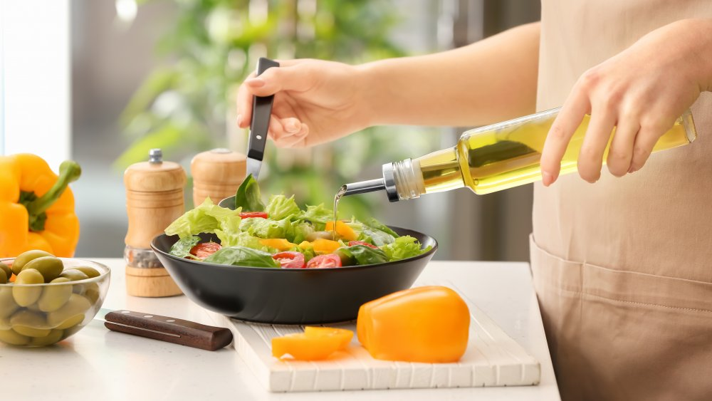 woman dressing salad with olive oil