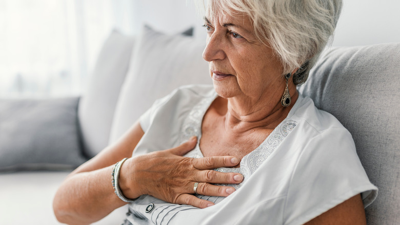 Older woman holding her chest in pain
