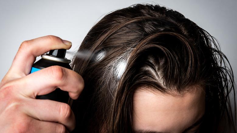 Woman spraying dry shampoo on hair
