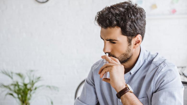Man using nasal spray in office