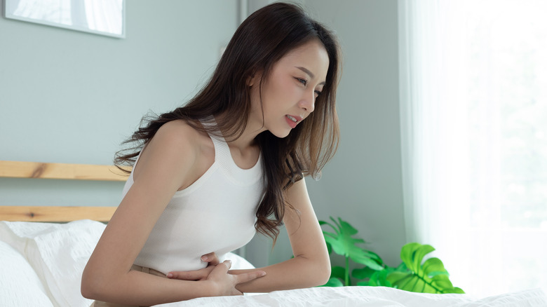 Woman sitting up in bed with hands on stomach
