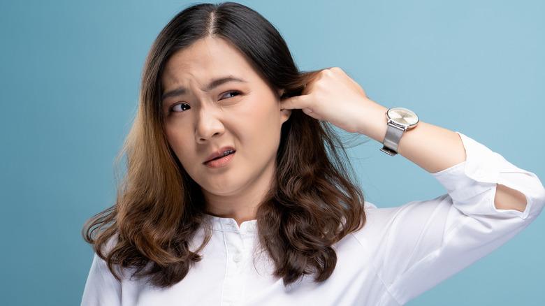 Woman sticking finger in ear