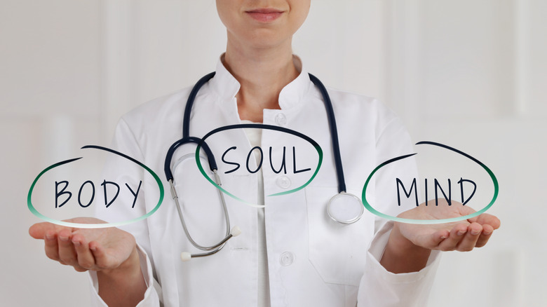 """A doctor holding out her hands. The words """"body"""", """"soul"""", and """"mind"""" are balanced between her hands"""