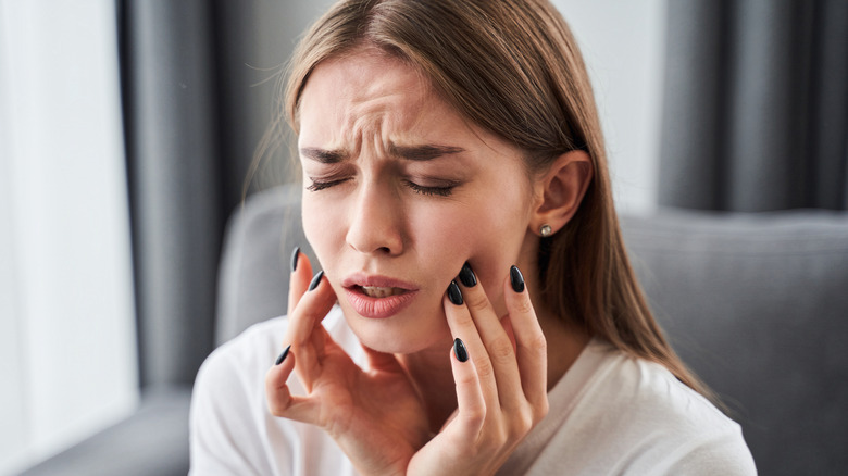 Woman with tooth pain grabbing face