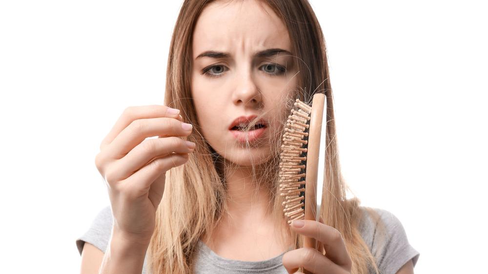 Light haired woman upset over hair in her brush