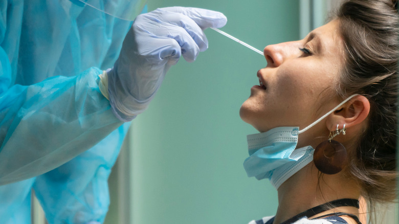 Healthcare worker with protective equipment performs COVID-19 swab test on woman