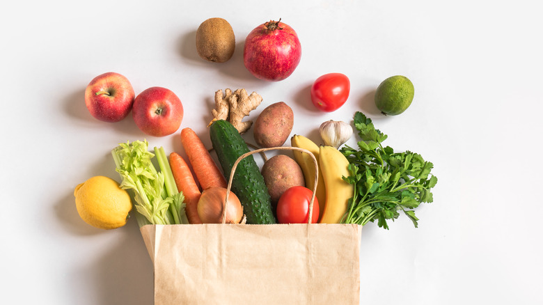 brown grocery bag spilling over with healthy foods