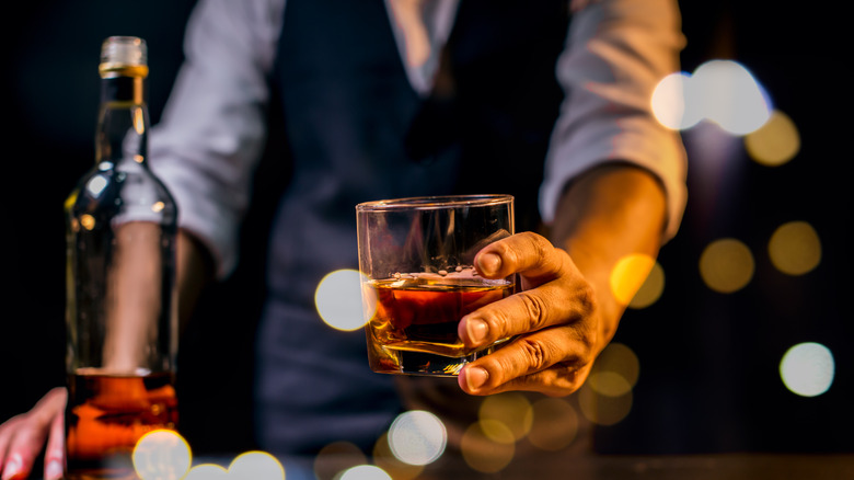 Man passing glass of whiskey